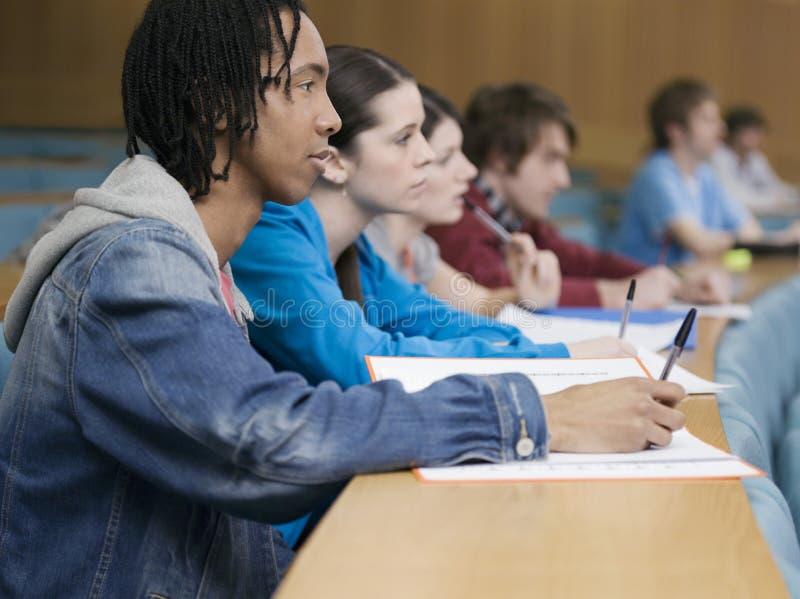Estudiantes universitarios que estudian en clase imagen de archivo libre de regalías