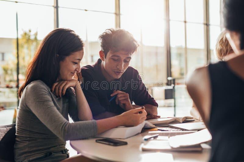 Estudiantes universitarios que estudian junto en clase imagen de archivo
