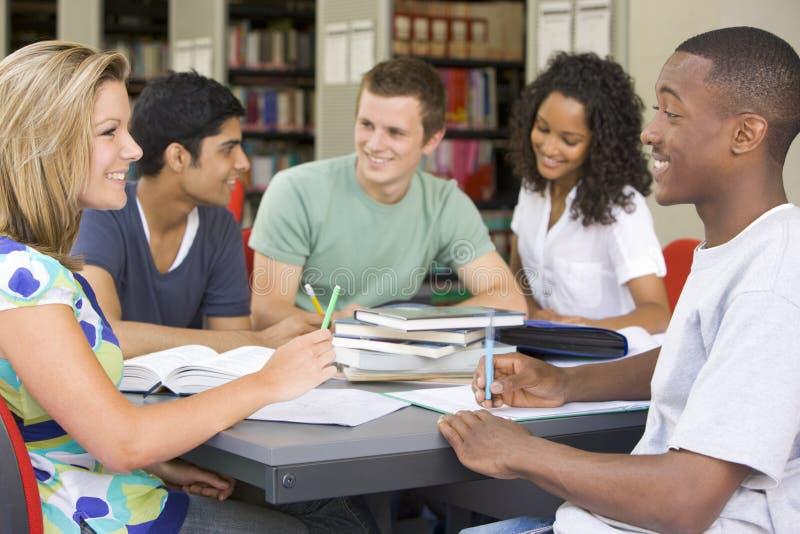 Estudiantes universitarios que estudian junto en una biblioteca imagen de archivo