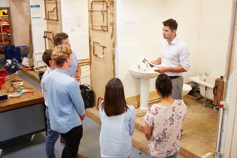 Estudiantes universitarios que estudian la fontanería que trabaja en el lavabo fotos de archivo