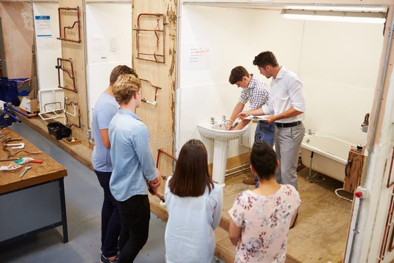 Estudiantes universitarios que estudian la fontanería que trabaja en el lavabo fotografía de archivo libre de regalías
