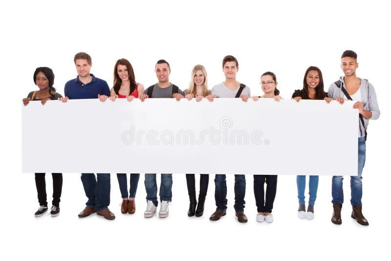 Estudiantes universitarios que exhiben la cartelera en blanco imagenes de archivo