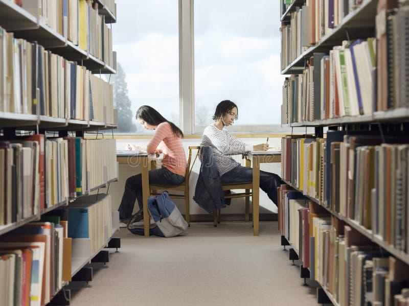 Estudiantes universitarios que hacen la preparación en biblioteca fotografía de archivo