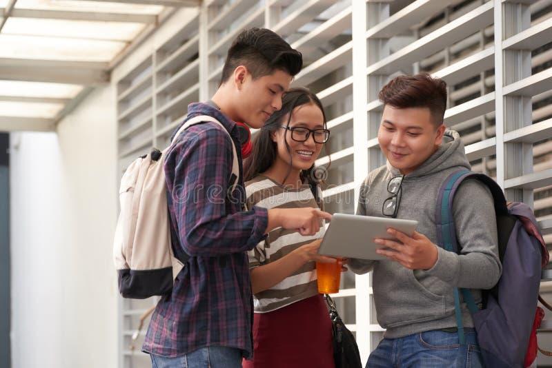 Estudiantes universitarios que intentan el nuevo app imagenes de archivo