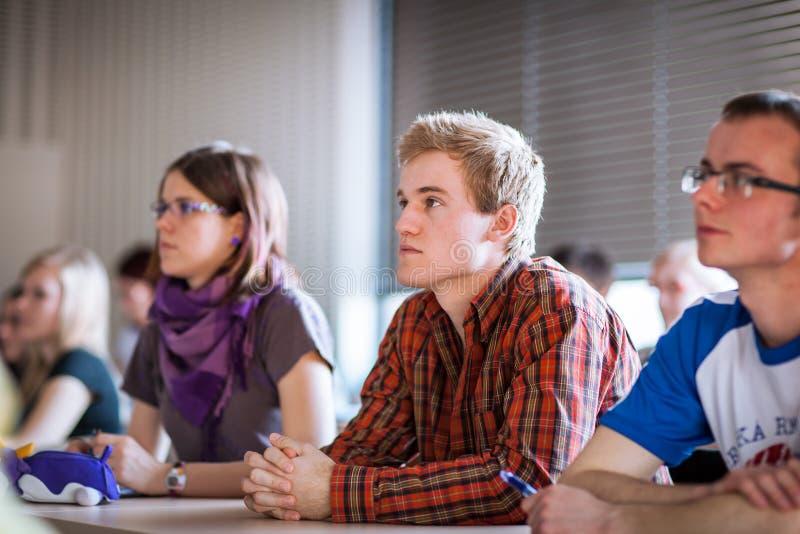 Estudiantes universitarios que se sientan en una sala de clase durante clase imágenes de archivo libres de regalías
