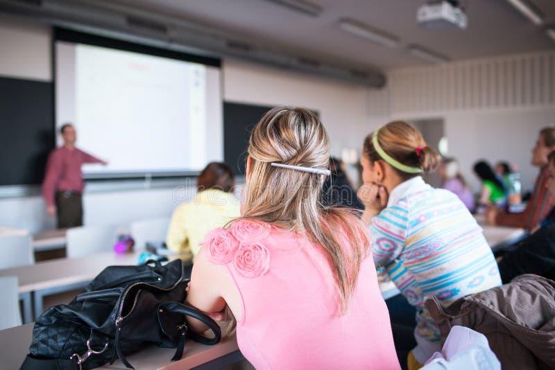Estudiantes universitarios que se sientan en una sala de clase durante clase fotos de archivo
