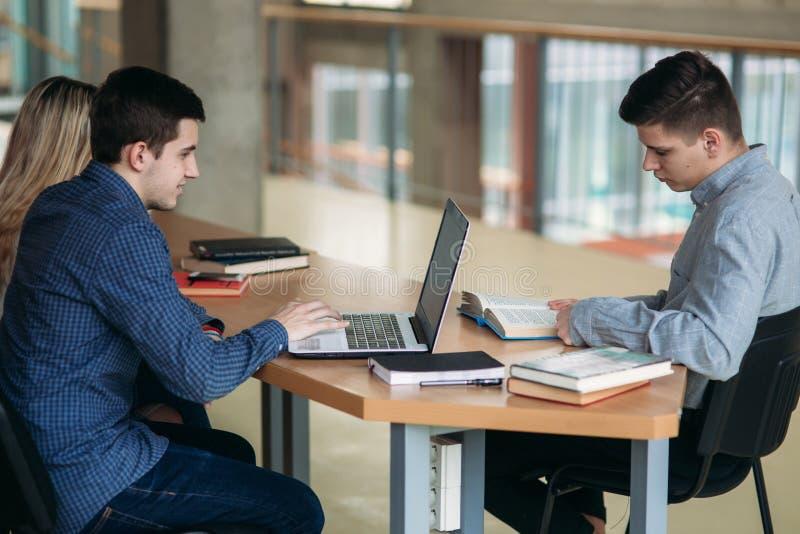 Estudiantes universitarios que se sientan junto en la tabla con los libros y el ordenador portátil La gente joven feliz que hace  imagen de archivo libre de regalías