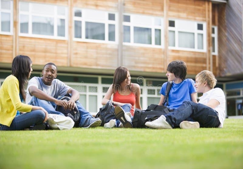 Estudiantes universitarios que se sientan y que hablan en césped fotos de archivo