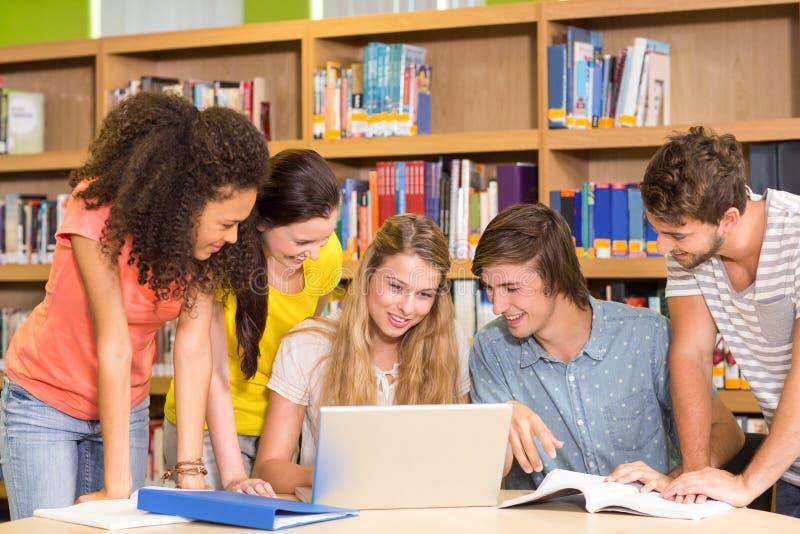 Estudiantes universitarios que usan el ordenador portátil en biblioteca imagenes de archivo