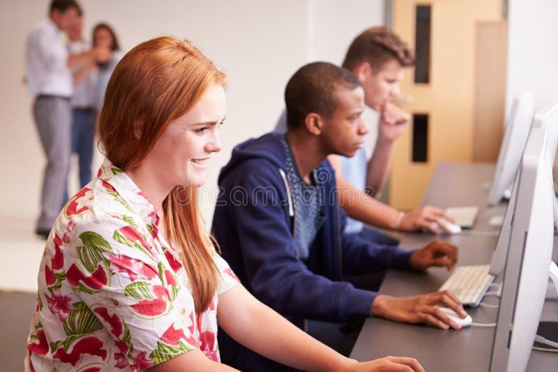 Estudiantes universitarios que usan los ordenadores en medios curso de estudios fotos de archivo libres de regalías