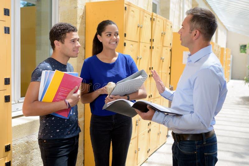 Estudiantes y profesor al lado de los armarios de la escuela secundaria foto de archivo
