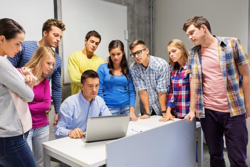 Estudiantes y profesor con el ordenador portátil en la escuela imagen de archivo libre de regalías