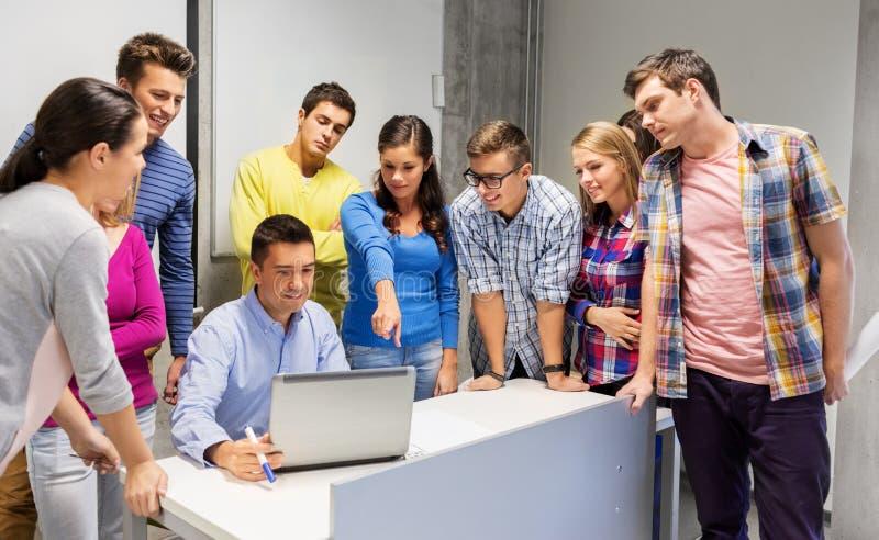 Estudiantes y profesor con el ordenador portátil en la escuela imagen de archivo