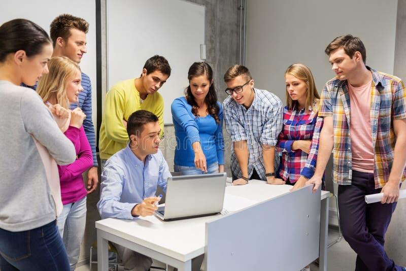 Estudiantes y profesor con el ordenador portátil en la escuela foto de archivo libre de regalías