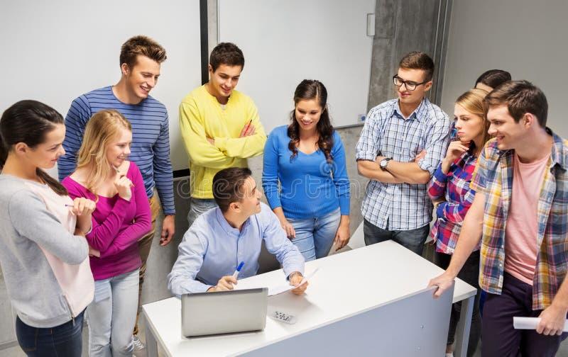 Estudiantes y profesor con los papeles y el ordenador portátil fotos de archivo