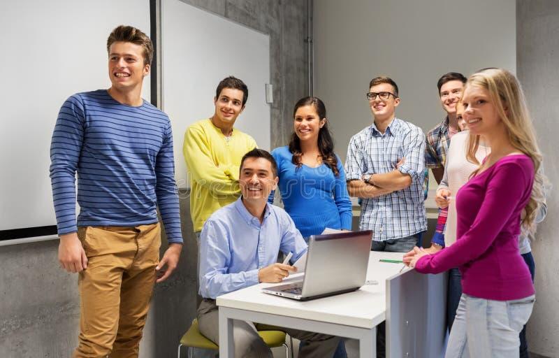 Estudiantes y profesor con los papeles y el ordenador portátil imágenes de archivo libres de regalías