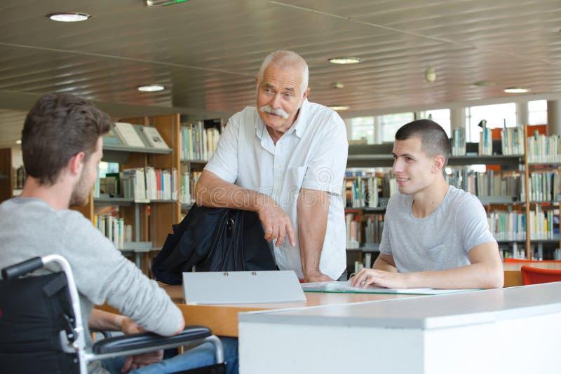 Estudiantes y profesor en biblioteca imagen de archivo libre de regalías