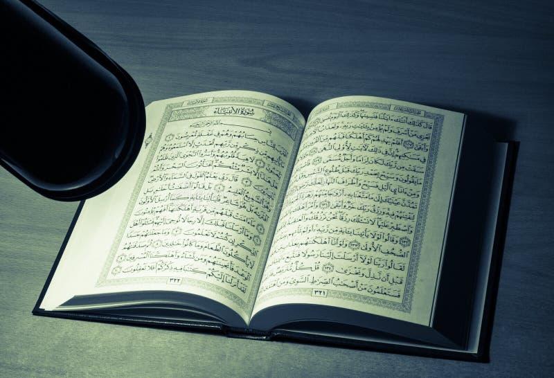 Estudiar quran en la noche detrás del escritorio fotos de archivo