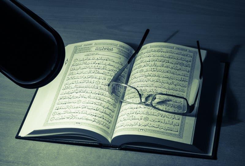 Estudiar quran en la noche detrás del escritorio foto de archivo
