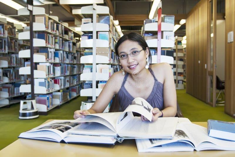 Estudio atractivo del estudiante femenino en la biblioteca imagenes de archivo