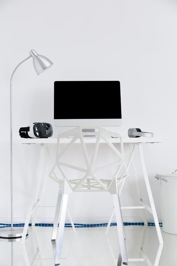 Estudio blanco con un ordenador, una lámpara y una silla del hueco imagen de archivo libre de regalías