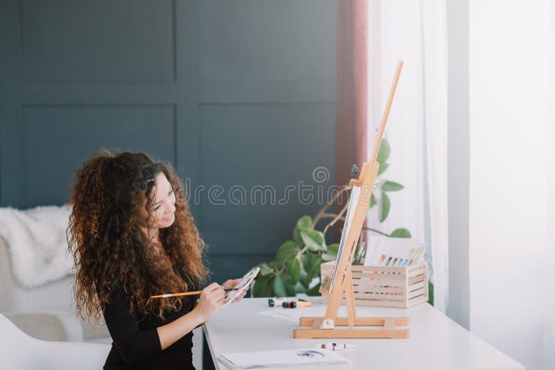 Estudio casero de pintura de la señora creativa de la afición del arte imagenes de archivo