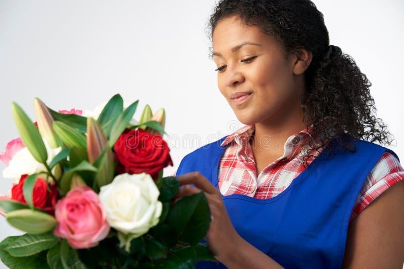 Estudio De Florista Femenina Organizando Un Bouquet De Nieves Y Roses Con Fondo Blanco imágenes de archivo libres de regalías