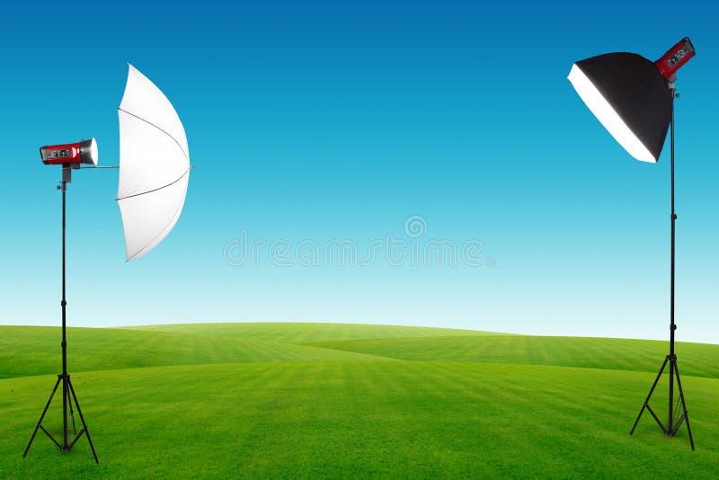 Estudio de la fotografía con una disposición ligera en campo de hierba verde imagen de archivo