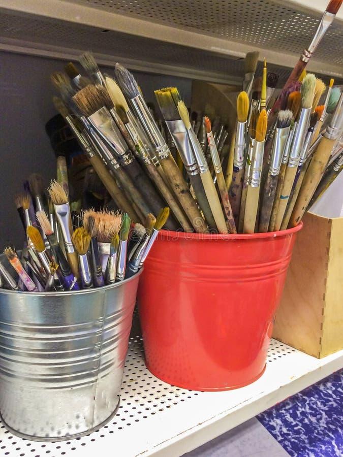 Estudio de la pintura Muchos cepillos sucios en rojo y cubos de la plata foto de archivo