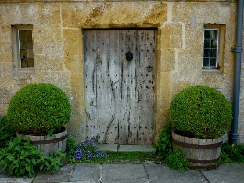 Estudio de la puerta de madera y de la piedra del viejo cotswold imagenes de archivo