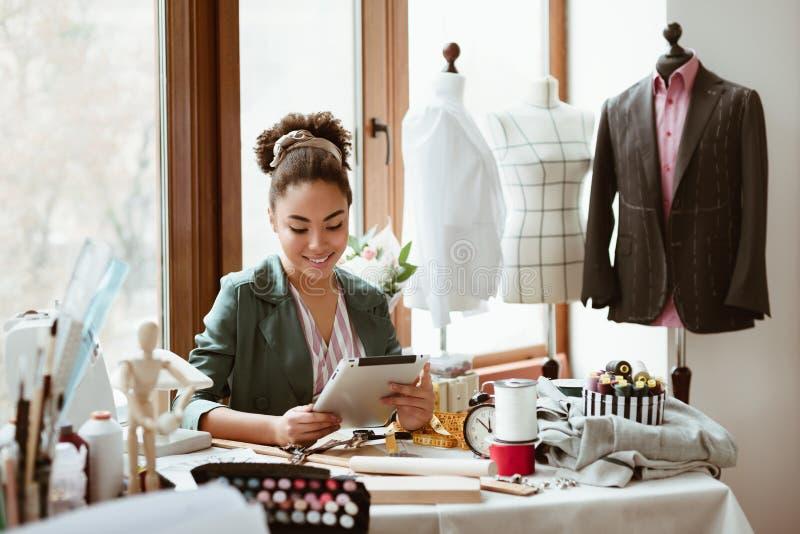 Estudio del diseño El sastre de la mujer joven con la tableta digital está modelando la nueva ropa imágenes de archivo libres de regalías