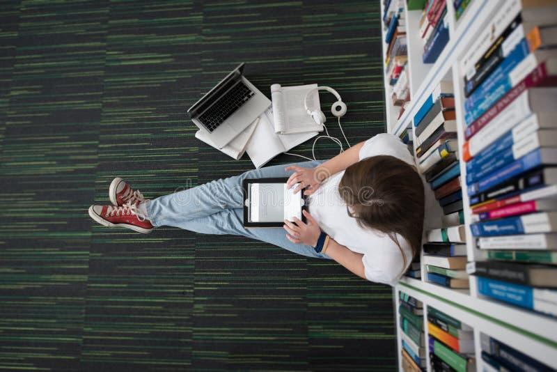 Estudio del estudiante en biblioteca, usando la tableta y la búsqueda para fotografía de archivo libre de regalías