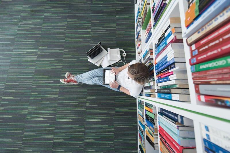 Estudio del estudiante en biblioteca, usando la tableta y la búsqueda para fotografía de archivo