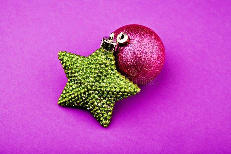 Estudio púrpura del fondo de la estrella del verde de la bola del juguete del Año Nuevo imagen de archivo