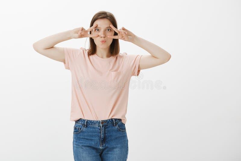 Estudio tirado de amigo femenino joven despreocupado emotivo en camiseta rosada con los tatuajes en los brazos, mostrando la mues fotos de archivo