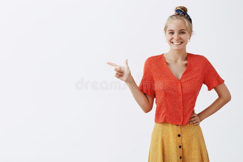 Estudio tirado de diseñador de sexo femenino joven emotivo feliz en blusa del vintage de moda y falda rojas de la mostaza, llevan imagenes de archivo