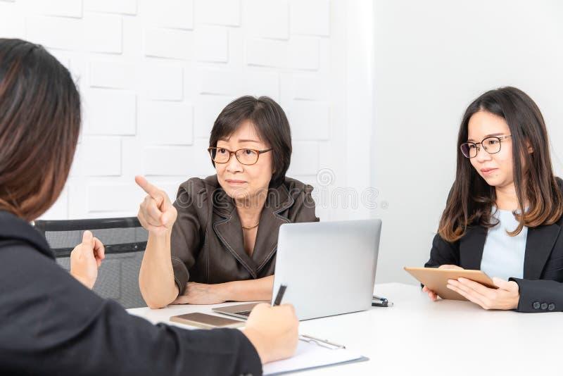 Estudio tirado de empresaria asiática, mayor con el ordenador portátil, sentándose con dos personales jovenes en sala de juntas e imagen de archivo
