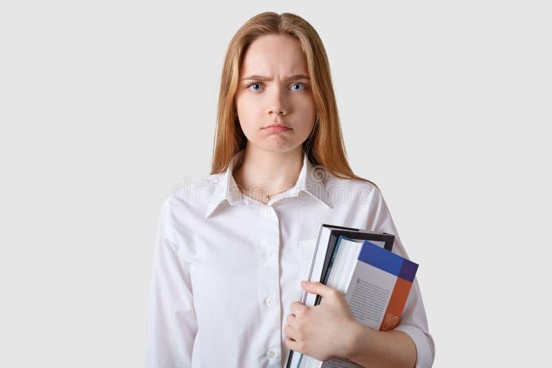 Estudio tirado de la mujer cabelluda marrón joven descontenta que mira directamente la cámara, presentando sobre el fondo blanco, foto de archivo