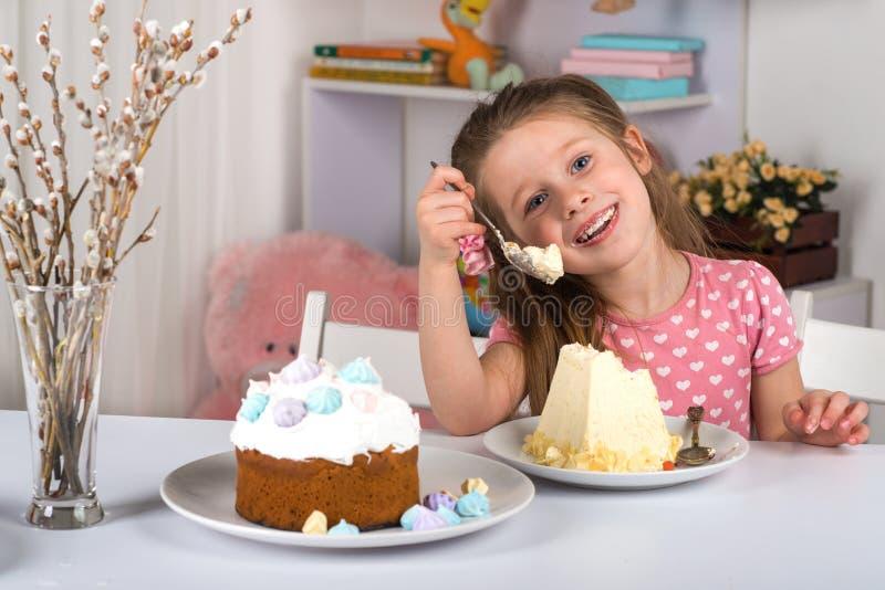 Estudio tirado de los pequeños niños, muchacha y muchacho, sentándose en una tabla con las tortas de Pascua Ella come el requesón imagenes de archivo