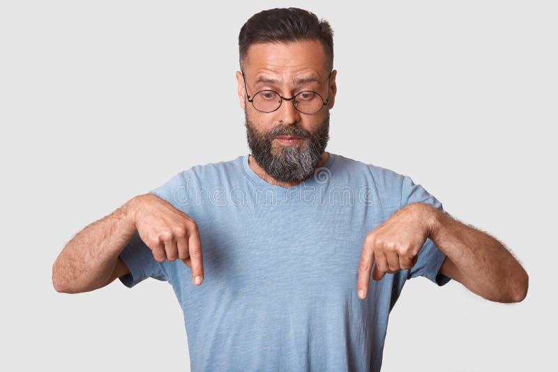 Estudio tirado de modelo carismático hermoso, de la camiseta casual azul que lleva y de lentes redondas, teniendo barba, haciendo fotos de archivo