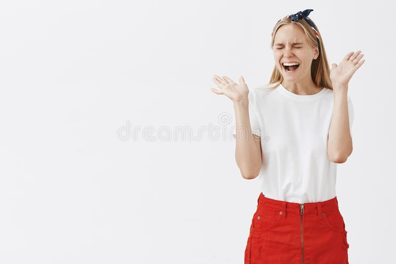 Estudio tirado de muchacha atractiva y elegante overemotive tonta con las palmas que agitan del excpression despreocupado y feliz imagen de archivo libre de regalías