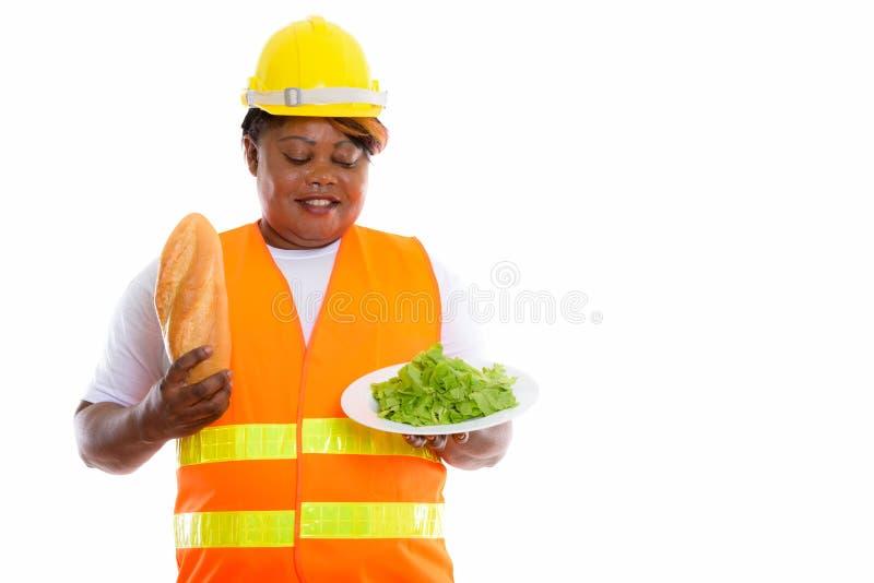 Estudio tirado de trabajador de construcción africano negro gordo feliz de la mujer foto de archivo