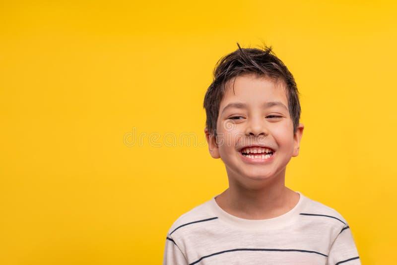 Estudio tirado de un muchacho de risa en una camiseta blanca en un fondo amarillo fotografía de archivo libre de regalías