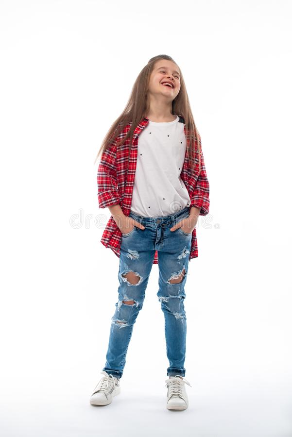Estudio tirado de una muchacha sonriente que lleva en vaqueros y de una camisa comprobada roja en un fondo blanco Ella ríe feliz  fotos de archivo