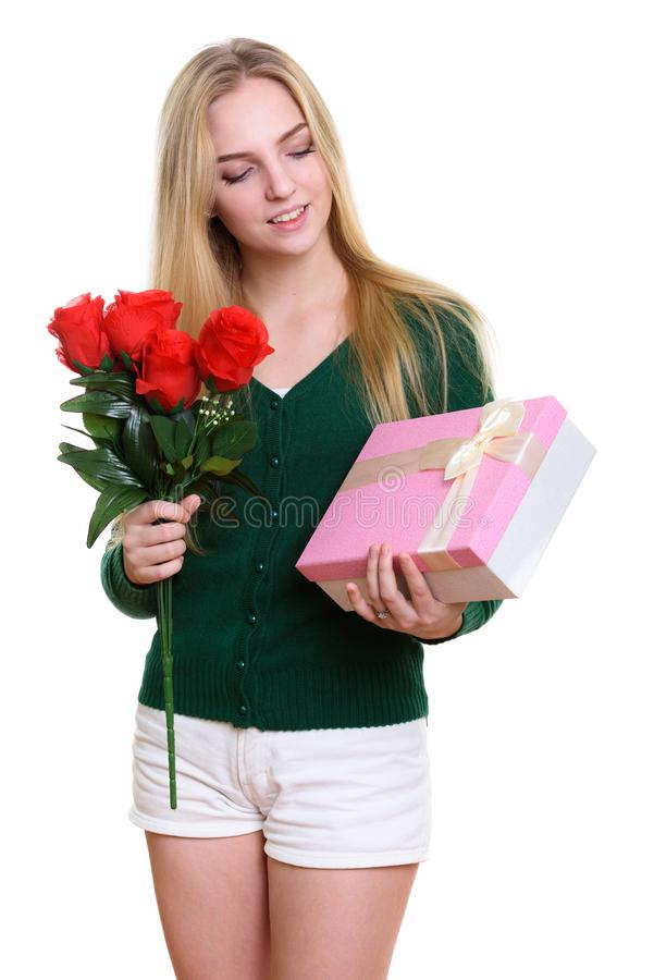 Estudio tirado del adolescente hermoso joven que sostiene rosas rojas fotos de archivo