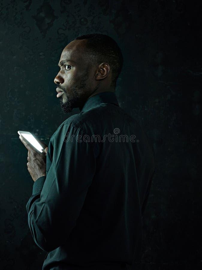 Estudio tirado del hombre africano negro serio joven que piensa mientras que habla en el teléfono móvil contra fondo negro fotos de archivo libres de regalías