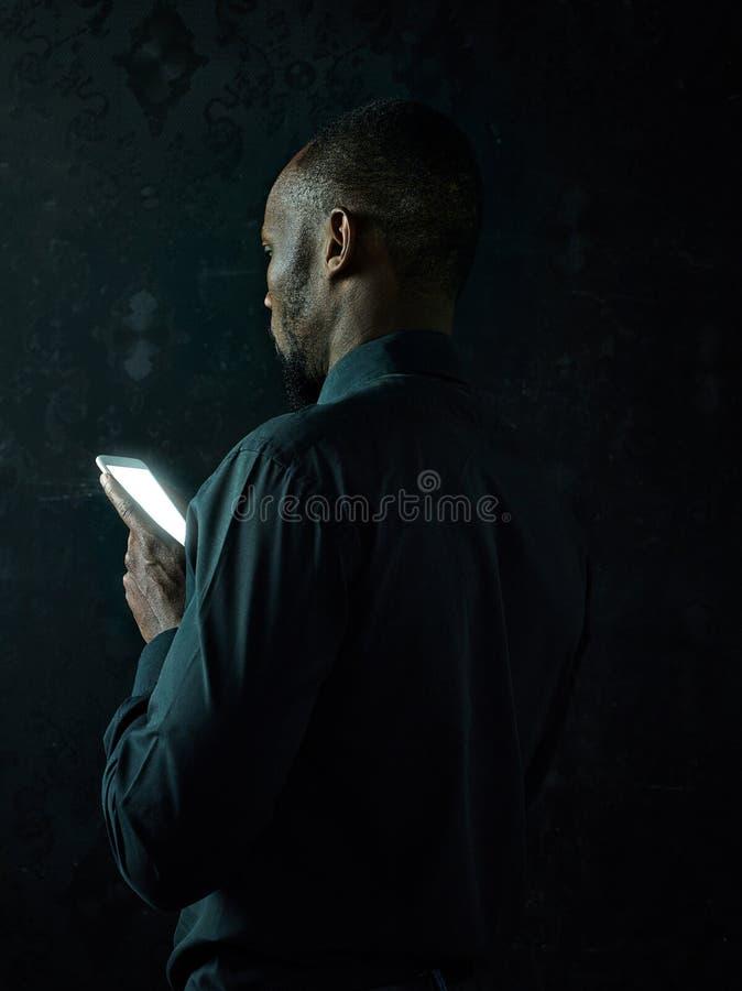 Estudio tirado del hombre africano negro serio joven que piensa mientras que habla en el teléfono móvil contra fondo negro imágenes de archivo libres de regalías
