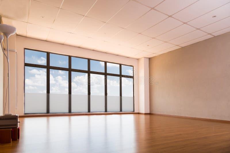 Estudio vacío de la yoga con el suelo de madera, ventanas con el cielo azul imágenes de archivo libres de regalías