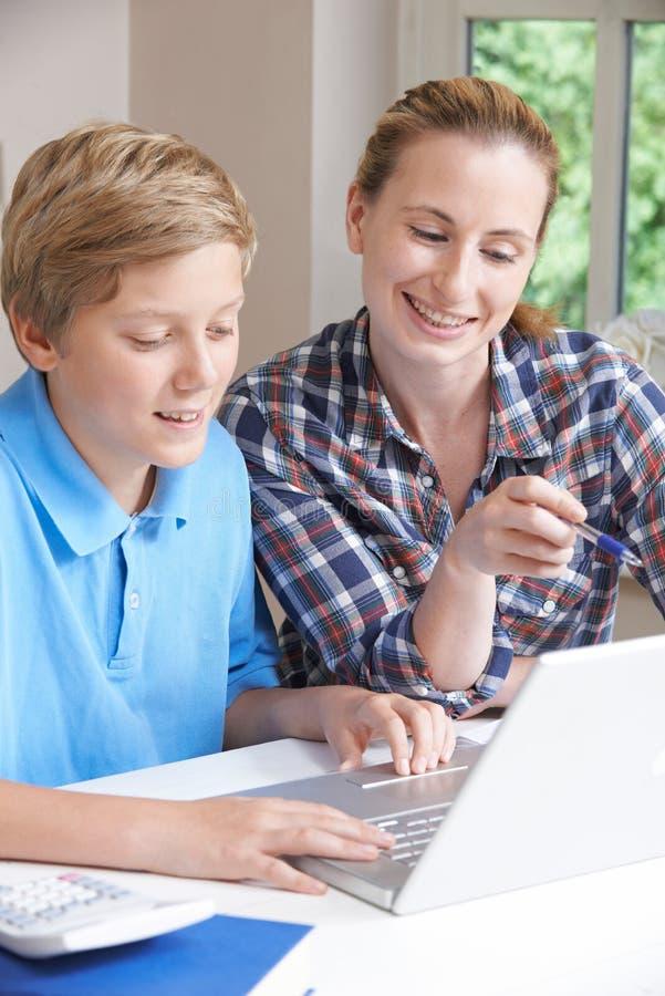 Estudios caseros femeninos de Helping Boy With del profesor particular usando el ordenador portátil foto de archivo libre de regalías