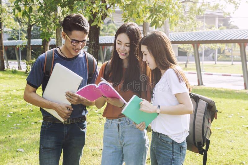 Estudo asiático do livro de leitura da educação do grupo que sorri com tabuleta, laptop no grupo do terreno da High School da uni imagem de stock royalty free